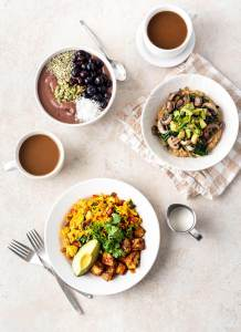 Three bowls of vegan breakfast foods on a light stone table top with cups of coffee