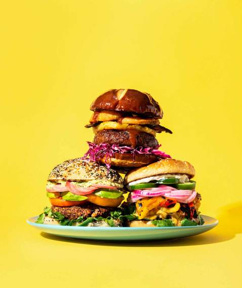 Three burgers in a stack on a teal plate, with a yellow background