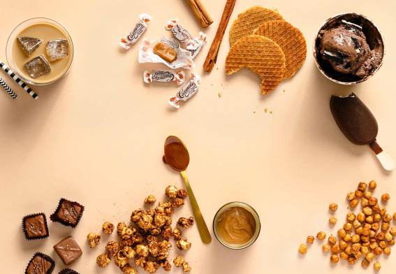 Various caramel-flavored foods shot on a beige/tan background