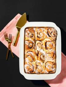 Casserole dish of cinnamon rolls on a pink linen, with gold serving ware on a black background