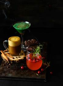Various seasonal cocktails shot on a vintage baking sheet with smoke on a black background