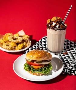 Burger on a white plate with chocolate cookie shake, and fried pickles on a red background