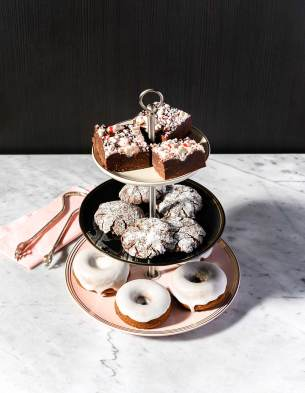 Dessert tower with donuts, cookies, and fudge on a marble table top