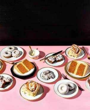 Multiple plates of desserts on a pink paper-lined table