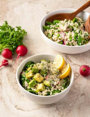 two bowls of couscous salad on a marble background