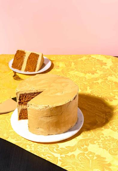 Pumpkin layer cake with slice cut out on a gold tablecloth with pink wall