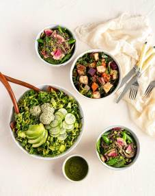 Several bowls of different types of salad on a light stucco background with cheesecloth on the side