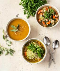 Three different soups pictured in bowls on a white wood background with spoons