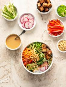 Spring roll bowl in a large white bowl, surrounded by small bowls of toppings