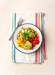 One bowl of creamy sweet potato noodles topped with mango, avocado, and tomatoes, on a striped linen